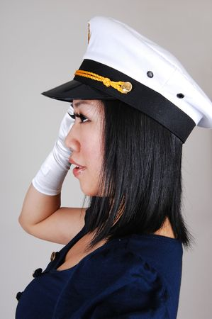 A young pretty Asian woman, in a sailor uniform and white gloves and sailor  a cap , in an portrait, standing saluting in the studio for light gray background. photo
