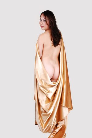 A beautiful young woman body, with her bum shooing, out of the fabric from gold satin, standing in the studio for light gray background.