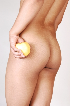 The gorgeous body of a young girl, shooing her butt , holding an apple in her hand, shooing a healthy lifestyle, for light gray background. photo
