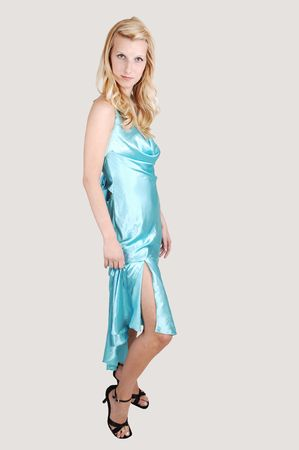 A beautiful tall blond woman in an light blue long dress and high heels standing from the site in the studio for a portrait, on light gray background. Stock Photo - 7037861