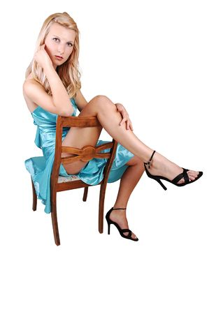 A beautiful tall blond woman in an light blue long dress and high heels sitting on an old chair, one leg one the back of the chair, on white background. photo