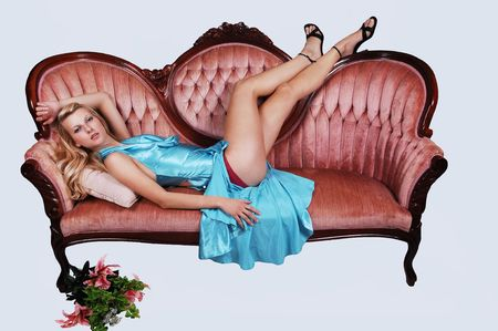 A young pretty woman with long blond hair and a light blue dress, lying on a pink sofa, shooing her nice long legs in high heels on light blue background. photo