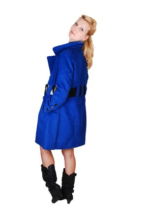 A pretty and tall woman in a blue winter coat and black boots standing in the studio, her hands in the pocket and looking over her shoulder,  for white background. photo