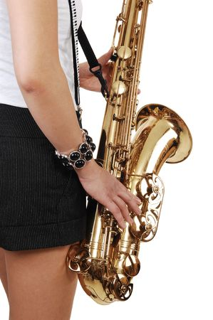 A young Asian woman standing in the studio, playing the saxophone in shorts with suspender, in closeup, for white background. photo