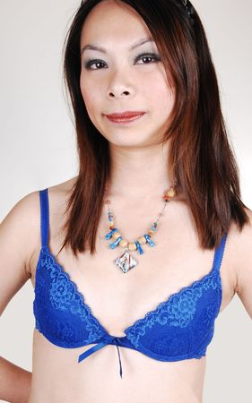 The portrait of a young pretty Chinese woman in a blue bra and very nice necklace with medium long brunet hair for light gray background. Stock Photo - 7072236