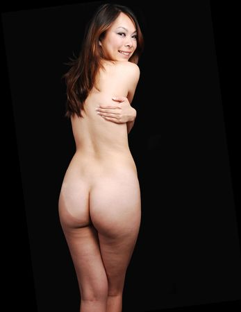 A beautiful young girls body, with her bum and nice legs shooing, hugging herself, standing in the studio for black background. Stock Photo - 7072182
