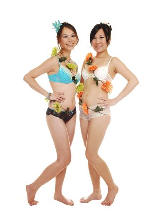 Two beautiful Asian woman in lingerie and nice flowers around  there bodies, standing feet in the studio for white background.  photo