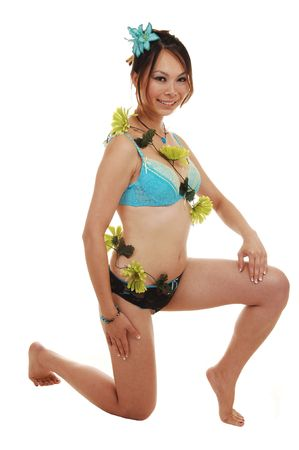 A young slime Asian woman kneeling in the studio in lingerie and some nice orange flowers around her body, for white background.  photo