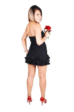 A young and pretty Asian woman in red high heels, a short black dress and a red rose in her hand standing with her back to the camera, looking over her shoulder, on white background. Фото со стока