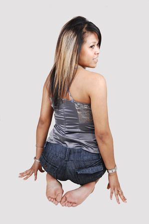 A young pretty Asian woman, in shorts and silver gray top, kneeling on the floor in the studio and looking over her shoulder, on white background. photo