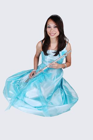 A young Asian woman in an light blue evening dress holding the flute sitting on the floor in the studio for light gray background. photo