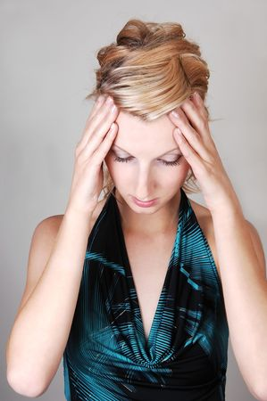 A beautiful blond woman holding her hands on her head to rap of  her hurting head, on light gray background. photo