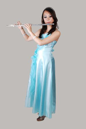 A young Asian woman in an light blue evening dress playing the flute standing on the floor in the studio for light gray background. photo