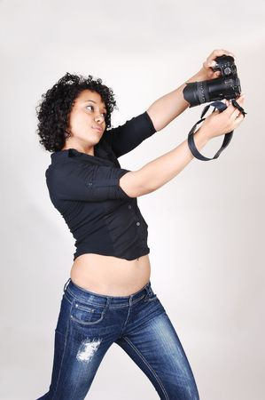 A pretty Hispanic woman try to take a picture of herself in a black blouse and jeans, over light gray. photo