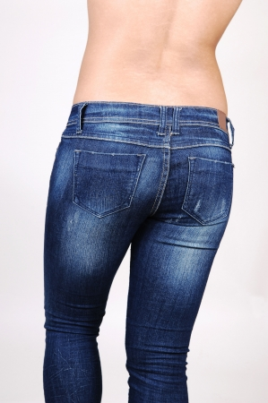 A topless Hispanic woman in jeans from the back, shooing her nice round butt, on light gray background. Stock Photo - 7124925