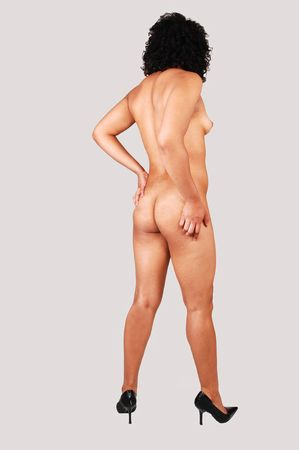 nude woman standing: A young pretty nude woman standing in the studio in high heels and curly black hair, shooing her beautiful body from the back, on light gray background.