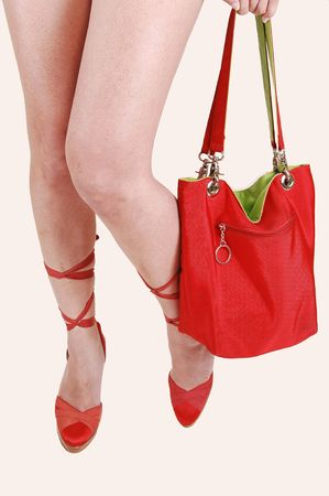 The legs of a young woman with red high heels, holding a red bag  with green fabric inside on light beige background. Stock Photo - 7157483