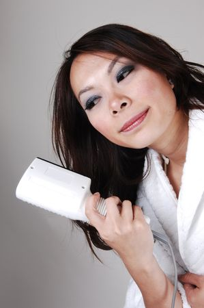 A pretty Chinese woman in a white bath robe is drying her hair with a electric hairdryer, for light gray background.