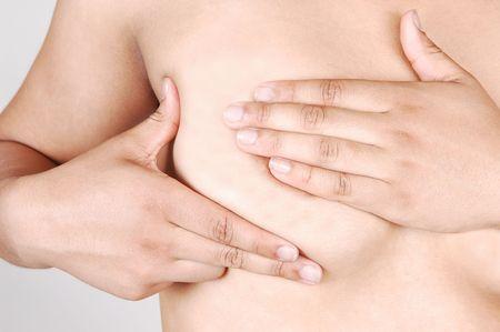 femme se deshabille: Une jeune femme examinant son sein droit pour voir si il les morceaux, qui pourrait �tre le cancer, pour allumer arri�re-plan gris.  Banque d'images