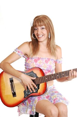 A beautiful woman sitting and playing the guitar in a light colorful short  top and skirt, for white background. photo