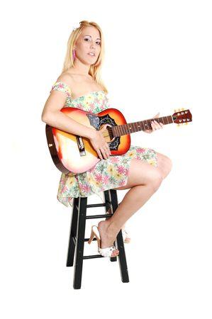 美しい女性の座っていると白い背景の明るいカラフルな短いトップとスカート、ギターを演奏します。