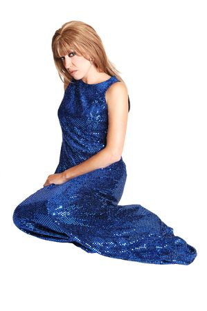 A brunette young pretty woman in a long navy blue dress sitting on the floor in the studio looking shy into the camera on white background. photo