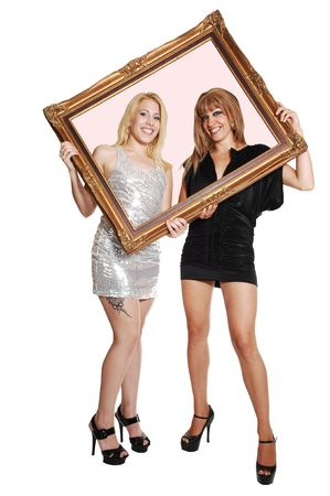 Two young woman, blond and brunette, in short evening dress and high heels, holding a picture frame up and looking trough, for white background. photo