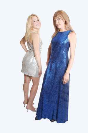 Two lovely woman, on in a silver short dress, the other one in a blue long dress standing side be side in high heels for light gray background.  photo