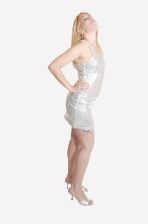 A pretty blond woman in a short silver dress and silver high heels standing in the studio for light gray background.  photo