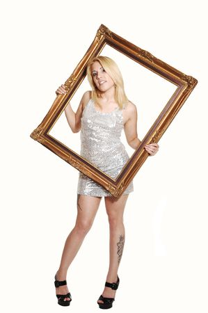 A young lovely woman holding up a picture frame and putting her upper  body trough, smiling, in high heels and silver dress, for white background.  photo