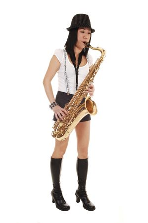 A young Asian woman standing in the studio, playing the saxophone in shorts with suspender and a hat on her black hair, for white background.