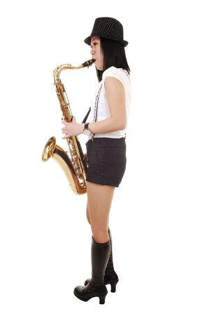suspender: A young Asian woman standing in the studio, playing the saxophone in shorts with suspender and a hat on her black hair, for white background.