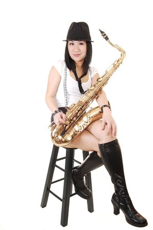 A young Asian woman sitting in the studio, playing the saxophone in shorts with suspender and a hat on her black hair, for white background.