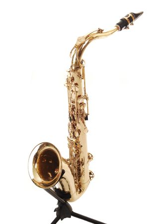 A beautiful brass saxophone on an black rack sitting on the floor of a studio for white background. photo