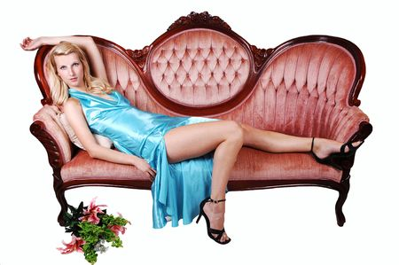 A young pretty woman with long blond hair and a light blue dress, lying on a pink sofa, shooing her nice long legs in high heels on white background. photo