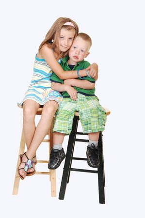 椅子の上に彼女の兄と一緒に座って、彼に大きなハグをきれいな女の子明るい青の背景に