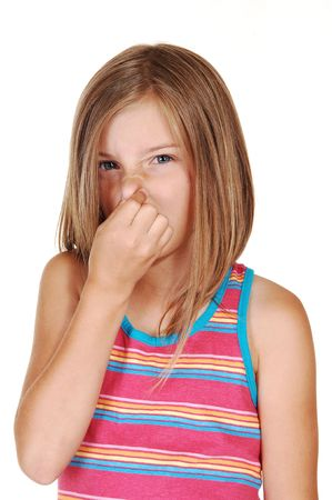 A lovely young girl with blond hair holds her nose closed for the smellin front of her, for white background. Archivio Fotografico