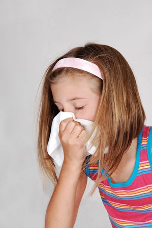 A beautiful young blond girl is sneezing in her tissue because of her cold, over light gray background.   photo