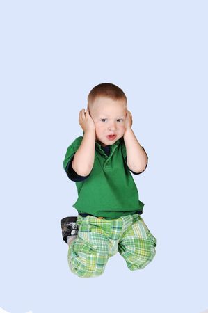 An little toddler boy holding his hands over his ears, he doesn't like to hear what her mother is telling him, over light blue background.  photo