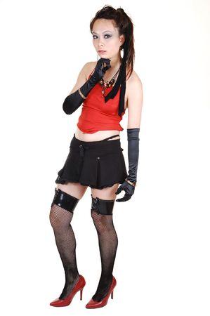 短い黒いスカート、黒ストッキングとクローブ スタジオ赤いハイヒール、白い背景の上に立っている若い中国の女性。