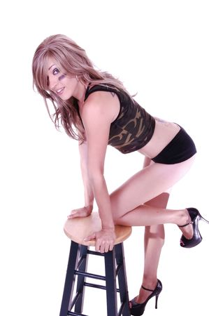 An blond young woman in lingerie kneeling on a bar chair in high heels and black clothing for white background. photo