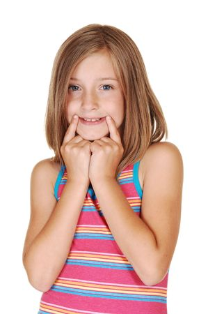 A young pretty girl stretched her mouth with her fingers to mimic a bright smile, on white background.