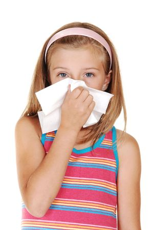 A beautiful young blond girl is sneezing in her tissue because of her cold, over light gray background.