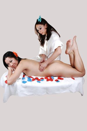 A pretty Asian woman, nude, getting a massage from a Chinese girl, lying on  a table with flower petals around her, for light gray background. Stock Photo - 7526586