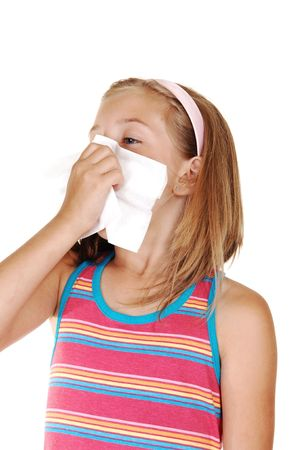 nose: A beautiful young blond girl is sneezing in her tissue because of her cold, over white background.