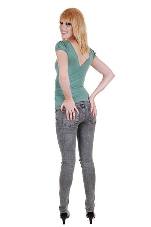 A young pretty and tall woman in jeans and green sweater standing from  the back in the studio, holding her butt, over white background.