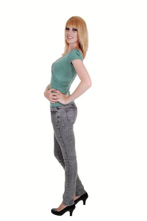 A beautiful tall and slim woman in gray jeans and green sweater standing in the studio in profile and smiling into the camera, on white background.