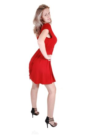 An very pretty tall woman in black high heels and a red dress standing in the studio with her long white blond hair, for white background. Stock Photo - 7732190