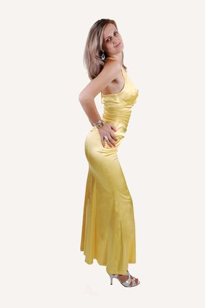 An elegant lovely woman in an long yellow, gold dress, showing her nice figure, with long white blond hair and silver heels standing in the studio for white background. photo