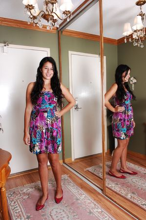 A lovely young woman standing in the entrance of an apartment, with her reflection in the mirror, in an colorful dress and long brunette hair.  photo